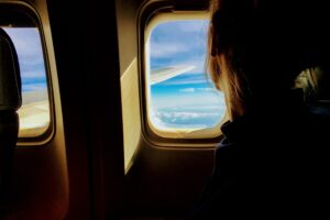 Tim Gouw - person looking outside of airplane window via Unsplash