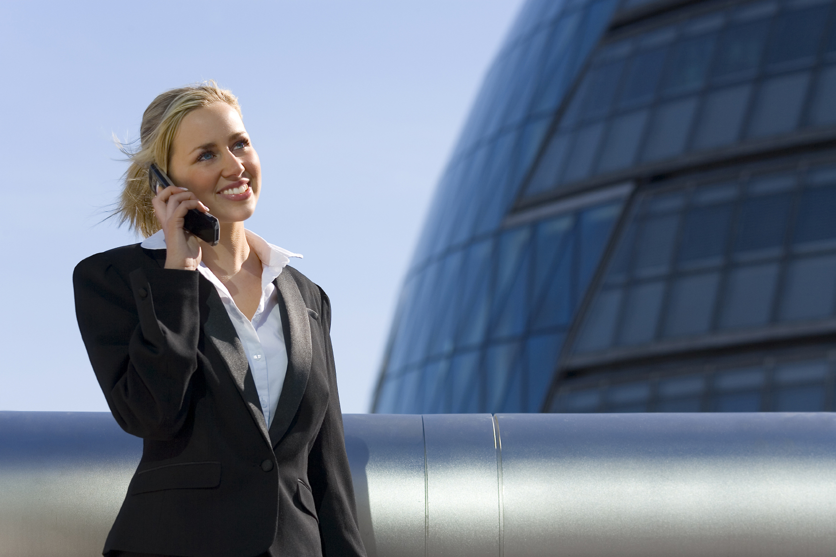 A beautiful young blonde executive using a mobile phone in a hi-tech surrounding.