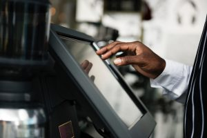 A cashier uses a touchscreen point-of-sale device.