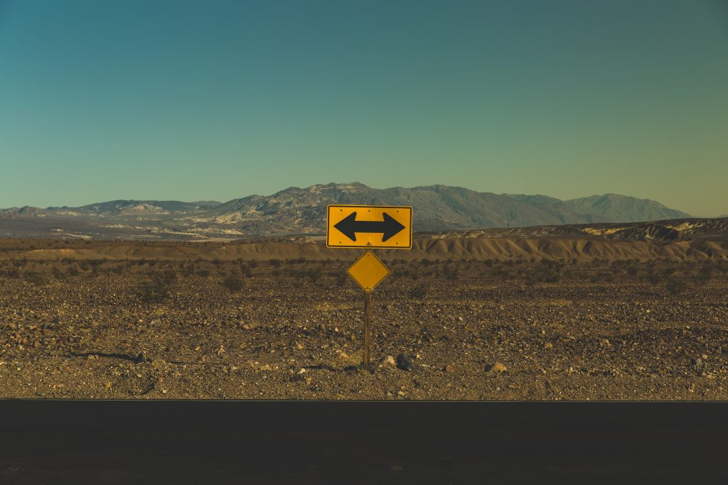 A road sign in Death Valley National Park shows arrows going in two directions.