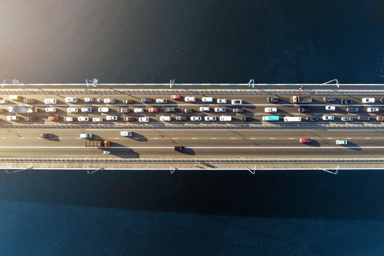 Aerial view of road bridge across river with heavy traffic jam in one direction. Rush hour with mash and overloading of road infrastructure. Resolving of car traffic jam